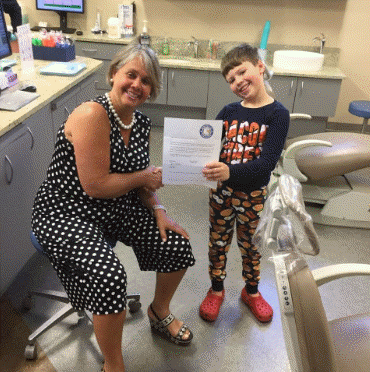 Photo of Dr. Ensor handing over a certificate to a pediatric patient